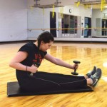 Row: Sit on the ground with your legs extended straight in front of you. Wrap an exercise band around your feet, and hold one end in each hand. Alternate pulling your hands back towards your chest and returning forward, leaning back and forward with each hand. If you don't have an exercise band, you can do this with dumbbells or by simply making a fist.